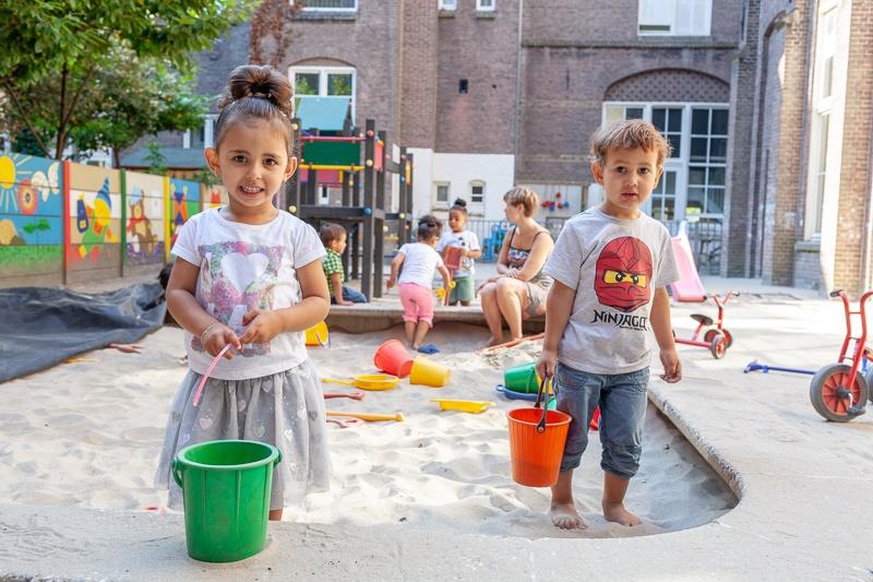 jongen en meisje spelen in zandbak met emmertjes
